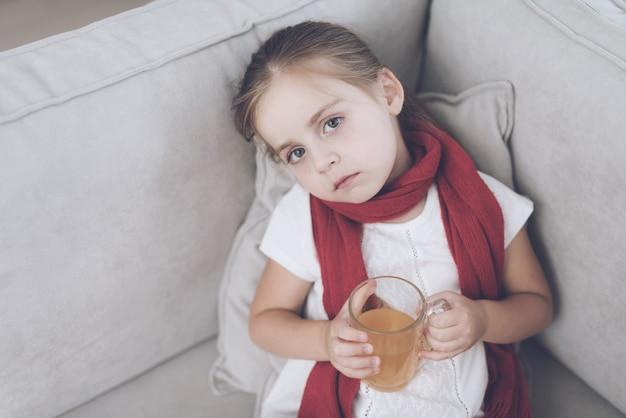 Mała chora dziewczyna z szklanką teon kanapy.