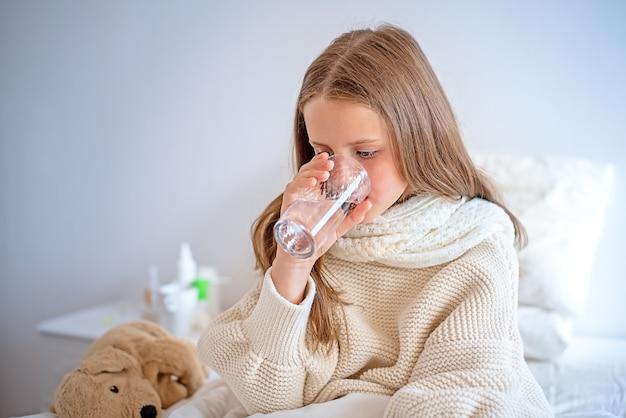 Mała chora dziewczynka siedząca na łóżku pije wodę.