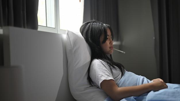 Mała chora dziewczynka w kocu leży na łóżku i mierzy temperaturę.