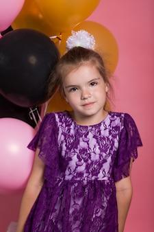 Mała ciemnowłosa dziewczyna z kolorowymi balonami