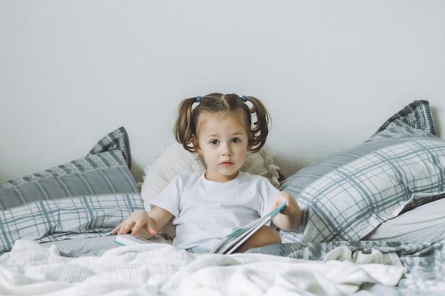 Mała ciemnowłosa dziewczynka 2-4 z dwoma kucykami siedzi na łóżku z poduszkami i czyta książkę