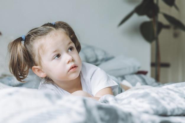 Mała ciemnowłosa dziewczynka z dwoma kucykami leży na łóżku na brzuchu