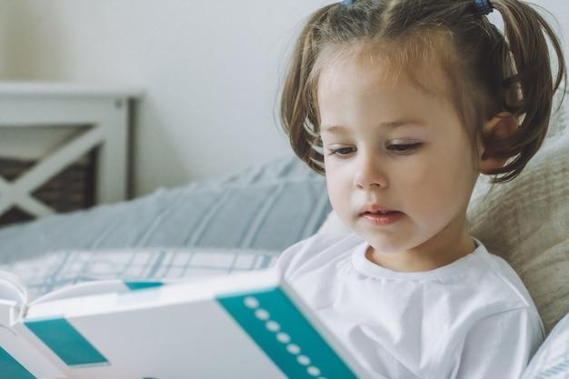 Mała ciemnowłosa dziewczynka z dwoma kucykami siedzi na łóżku z poduszkami i czyta książkę