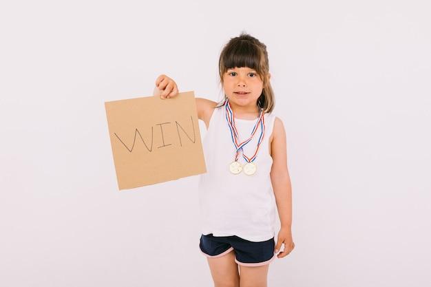 """Mała ciemnowłosa dziewczynka z medalami mistrza sportu, trzymająca tabliczkę z napisem """"wygraj"""". koncepcja sportu i zwycięstwa"""