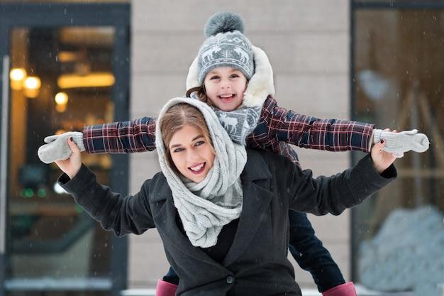 Mała córka bawić się z matką w zimowym mieście