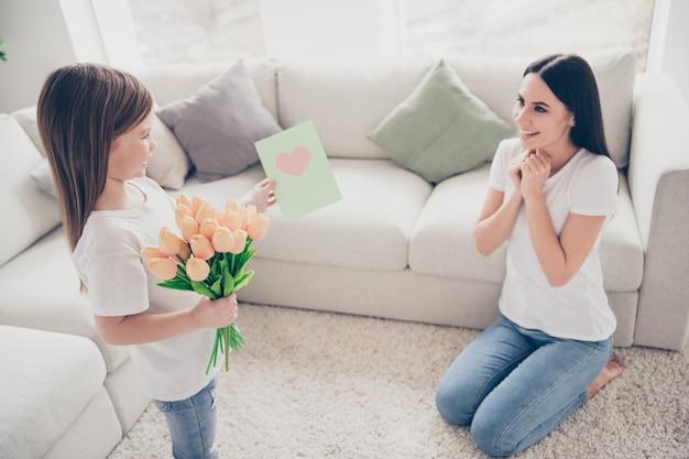 Mała córka daje mamie pocztówkę z bukietem róż w domu w domu
