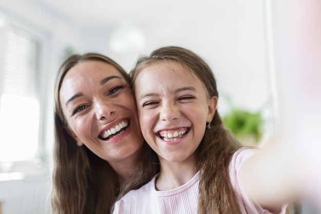 Mała córka młoda matka twarze kamery z bliska widok. urocza dziewczynka używa smartfona baw się ze starszą siostrą robiąc zdjęcia selfie, vlogerzy nagrywają nowy vlog, ciesz się zabawną koncepcją aktywności