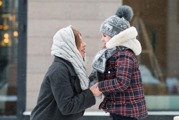 Mała córka patrząc na matkę z miłością w zimowym mieście