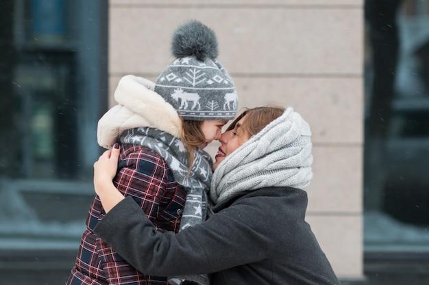 Mała córka stoi twarzą w twarz z matką w zimowym mieście.