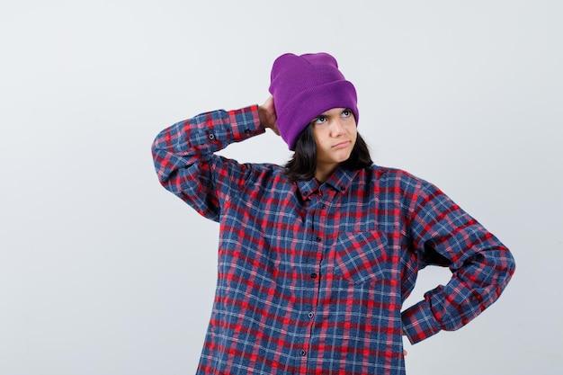 Mała czapka kobieca trzymająca rękę na biodrze, trzymająca dłoń na głowie, wyglądająca na zamyśloną
