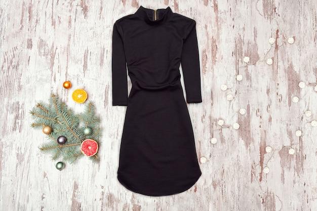 Mała czarna sukienka z rękawami i świerkową gałązką na drewnianym tle. modna koncepcja