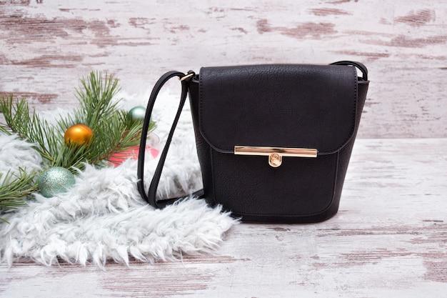 Mała czarna torebka damska na drewnianej, jodłowej gałęzi z dekoracjami. koncepcja mody
