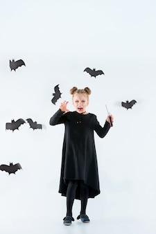 Mała czarownica dziewczyna w czarnej długiej sukni i magicznych akcesoriach. halloween.
