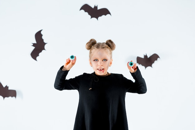 Mała czarownica dziewczyna w czarnej długiej sukni i magicznych akcesoriach. halloween