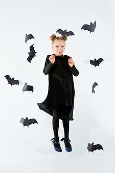 Mała czarownica dziewczyna w czarnej długiej sukni i magicznych akcesoriach.