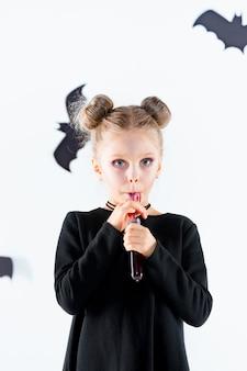 Mała czarownica dziewczyna w czarnej długiej sukni i magicznych akcesoriach