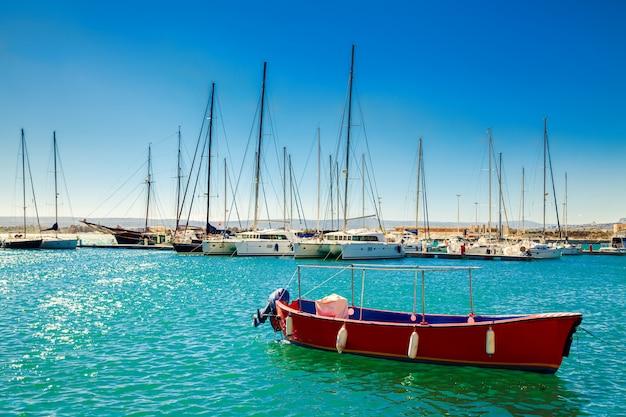 Mała czerwona łódź przed jachtami