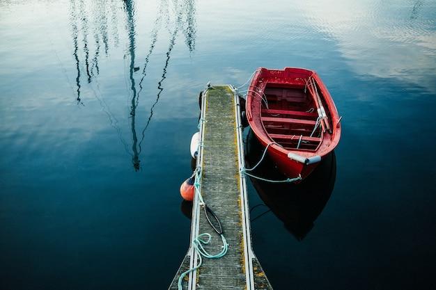 Mała czerwona łódź rybacka na mini porcie
