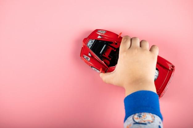 Mała czerwona zabawka samochodowa dla dziecka, bawiącego się z nią dziecka