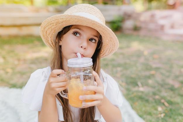 Mała dama o brązowych oczach i długich czarnych rzęsach odwracająca wzrok przy piciu soku owocowego. cute girl trzymając kieliszek koktajl i ciesząc się tym zimnym napojem w parku podczas wakacji.