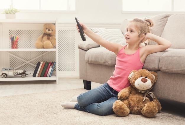 Mała dorywczo dziewczyna ogląda telewizję w domu. dziewczynka siedzi na dywanie podłogowym ze swoim pluszowym misiem, trzymając pilota i przełączając kanały, kopiując przestrzeń