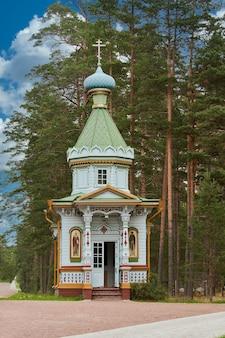 Mała drewniana cerkiew na tle drzew leśnych. drewniany kościół w lesie