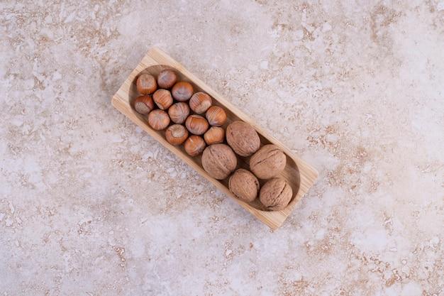 Mała drewniana deska pełna zdrowych orzechów włoskich