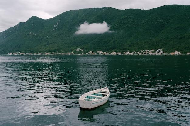 Mała Drewniana łódka Z Wiszącą Nad Nią Białą Chmurą. Streszczenie Tło Z Pojęciem Depresji. Wysokiej Jakości Zdjęcie Premium Zdjęcia