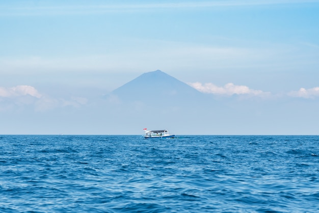 Mała drewniana łódź na błękitnym oceanie z jasnym niebem agung na tle i górą.