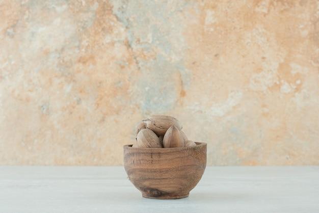 Mała drewniana miska orzechów na białym tle. wysokiej jakości zdjęcie