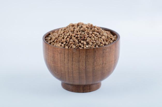 Mała drewniana miska pełna gryki na białym tle.