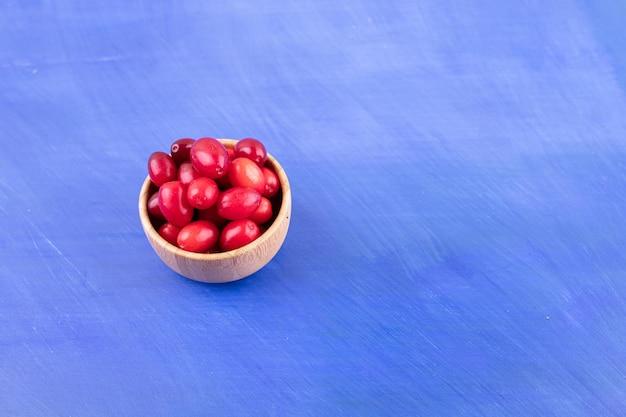 Mała drewniana miska pełna owoców dzikiej róży na niebieskiej powierzchni
