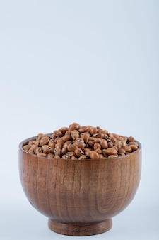 Mała drewniana miska pełna surowej, brązowej fasoli