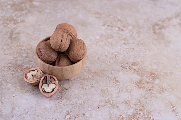 Mała drewniana miska pełna zdrowych orzechów włoskich