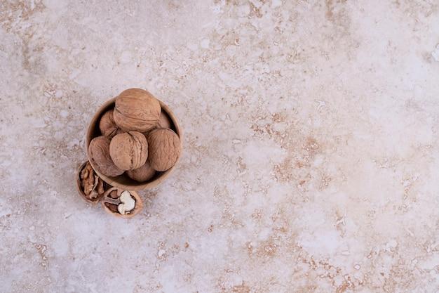 Mała drewniana miska pełna zdrowych orzechów włoskich.