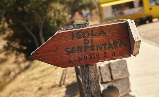 Mała drewniana tablica informacyjna cpn napisana wyspa serpentara pływanie 2 godziny