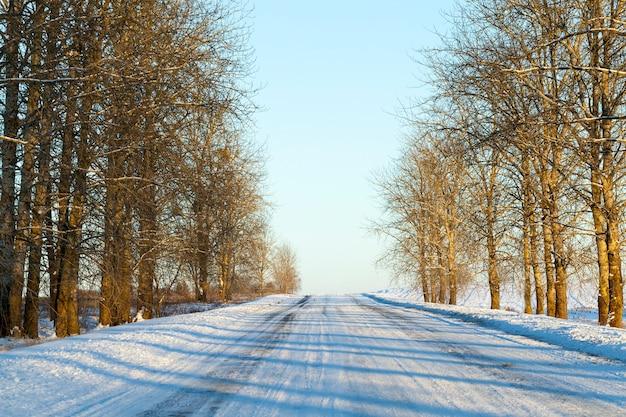 Mała droga pokryta śniegiem w sezonie zimowym, zbliżenie z małą głębią ostrości