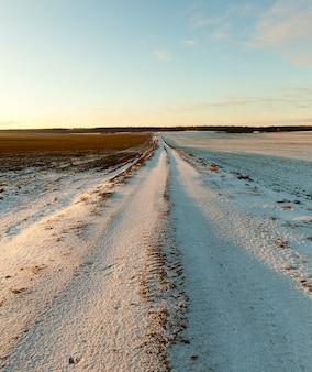 Mała droga w sezonie zimowym pokryta śniegiem. zbliżenie fotografii z płytką głębią ostrości