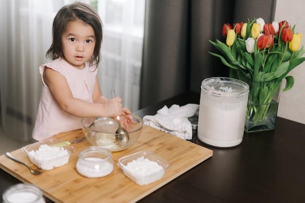 Mała dwulatka ubrana w białą sukienkę miesza jajko łyżką ze stali nierdzewnej