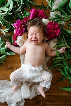 Mała dwumiesięczna dziewczynka leży na drewnianym stole z piwonkami i płacze.