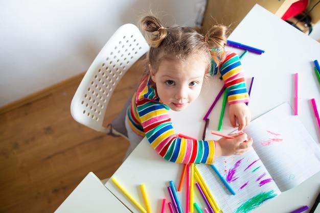 Mała dziewczynka, 3-letnia dziewczynka z kucykową fryzurą w wielokolorowej kolorowej kurtce w paski na lekkiej ścianie przy stole rysuje wielokolorowe markery i uśmiecha się