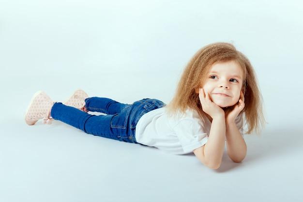 Mała dziewczynka 4 lata z kręconymi włosami na sobie białą koszulę, niebieskie dżinsy leżące na podłodze, uśmiechnięte i wyglądające, ręce trzyma głowę