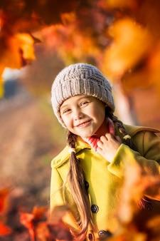 Mała dziewczynka 5 lat z jesiennych liści klonu się śmieje