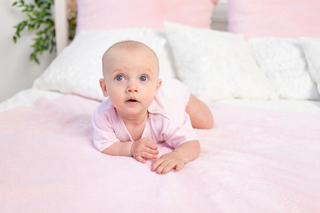 Mała dziewczynka 6 miesięcy czołganie się na białym i różowym łóżku w domu, odwracając wzrok, miejsce na tekst