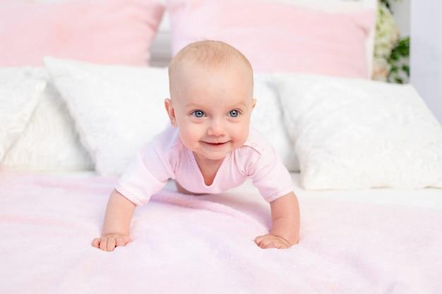 Mała dziewczynka 6 miesięcy czołganie się na różowo-białym łóżku, odwracając wzrok, miejsce na tekst