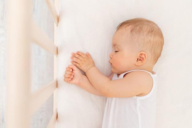 Mała dziewczynka 6 miesięcy śpi w białym łóżku