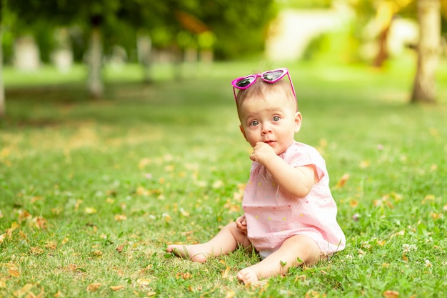 Mała dziewczynka 7 miesięcy siedzi na zielonej trawie w różowym body i jasnych okularach, spacerując na świeżym powietrzu