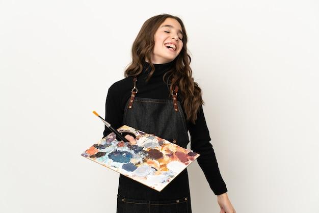 Mała dziewczynka artysta trzyma paletę na białym tle na białym tle, śmiejąc się
