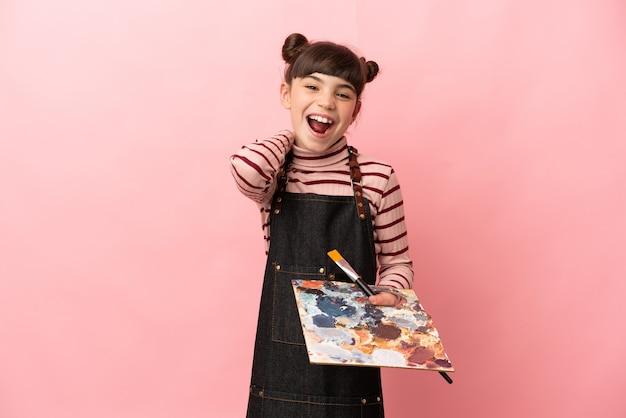 Mała dziewczynka artysta trzyma paletę na białym tle na różowy śmiech