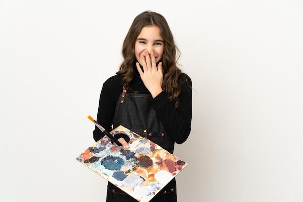 Mała dziewczynka artysta trzyma paletę na białym tle szczęśliwy i uśmiechnięty obejmujące usta ręką